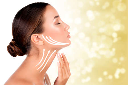 Pretty woman touching her neck on golden blurred background. Anti-aging concept.