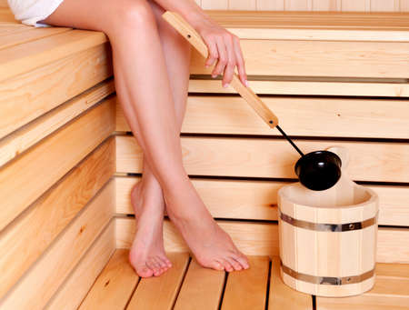 Woman wrapped in white towel sitting on the bench in a traditional sauna
