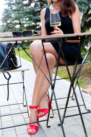 Beautiful woman with long sexy legs having a rest in the street restaurant . Model sitting in an armchair in a cafe