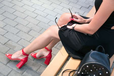 Long legged woman sitting on a bench Stock Photo