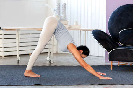 Young sporty woman practicing yoga, working out, wearing sportswear, white pants and grey top Stock Photo
