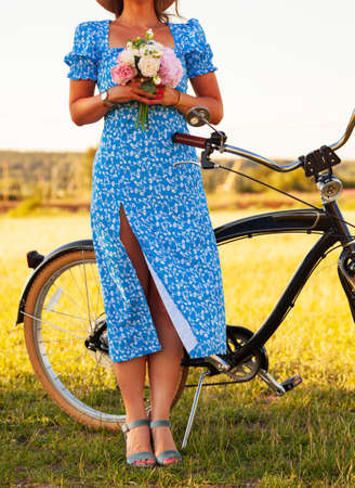 Woman in blue dress with a bicycle Stock Photo