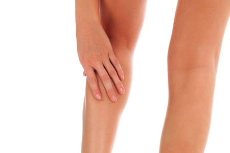 Woman touches her painful shin, isolated on white background