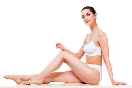 Pretty woman with slim beautiful body sitting against white background, isolated Stock Photo