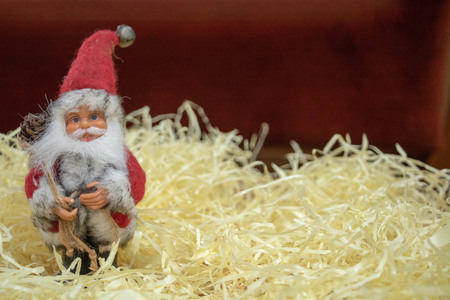 Santa Claus Figurine on straw and red background