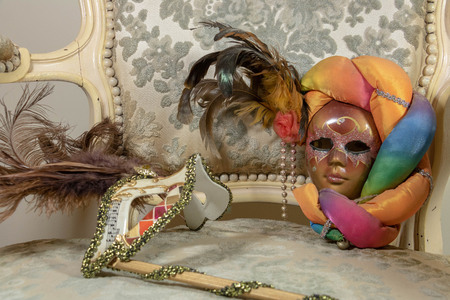 Different styles of carnival masks on rococo wing chair Stock Photo