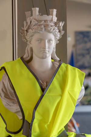 Marianne symbol of the French Republic with a yellow vest, facing angry French during the national debate of the citizen consultation