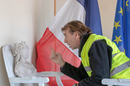 Yellow vests Man (Yellow Vest) threatening Marianne the symbol of France during the consultation