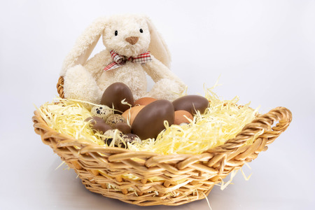 Easter bunny in a wicker basket with Easter eggs