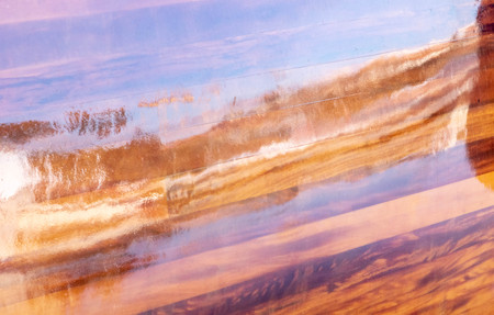 Reflections of the sea on a boathouse varnish mahogany color