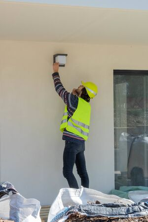 Foreman checking the installation of exterior lighting on a building under construction site visit