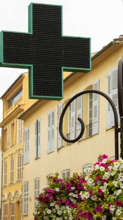 Green cross for pharmacy storefront - medical profession, with a floral decoration in the old Antibes.