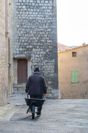 Rural scene in the south of France in Provence, an old man in a medieval village pulling a wheelbarrow in the streets to make life easier in an urbanization difficult to access