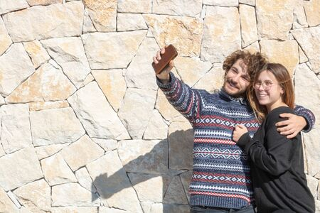 Young happy smiling couple taking a selfie on their smartphone during their holidays