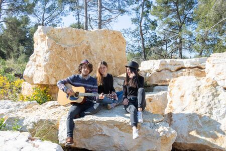 Group of happy young people having a barbecue in nature and singing around a guitar player Stok Fotoğraf
