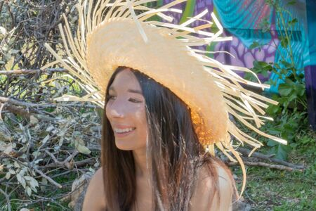 Young South American woman with a straw hat on the beach in the countryside, having fun and smiling Imagens