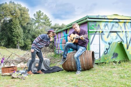 family, fathers day and friends, picnic in the country with a young man dancing while his father plays the guitar. Harvest Festival or birthday party 写真素材