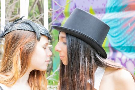 Multiracial homosexual women kissing during a steampunk picnic in a urbex gathering, with a top hat and a bibi hat with veil 写真素材