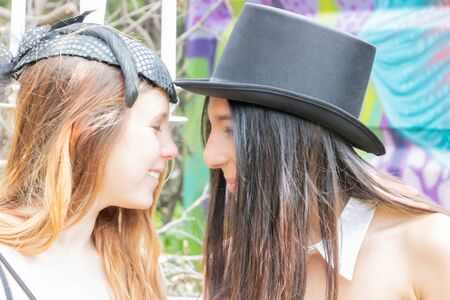 Happy lesbian couple with black hat and sailboat bibi in steampunk outfit at a celebration in an urbex place