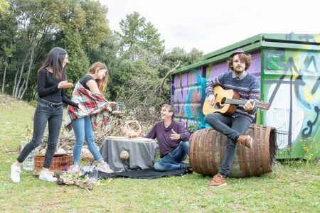 Happy man receiving a gift from his daughters while his son plays guitar during a picnic in the countryside