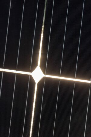 Close-up of a photovoltaic cell receiving sunlight and whose reflection forms a christian luminous cross