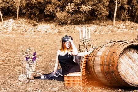 Young woman in evening dress and hat with veil, vintage style and steampunk during harvest