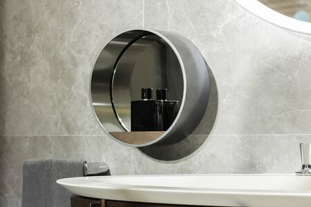 Detail on the round mirror of a modern steel bathroom with a bottle of perfume for men