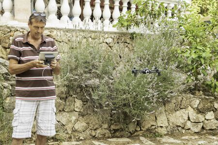 Retired senior man driving his drone in his garden in Provence south of France in front of a lavender and a lemon tree
