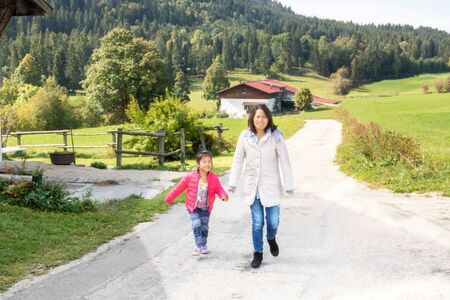 Family walk with Mom - Eurasian girl French and Chinese Metis walking with her Chinese mother in the countryside on the edge of forest in Franche Comté