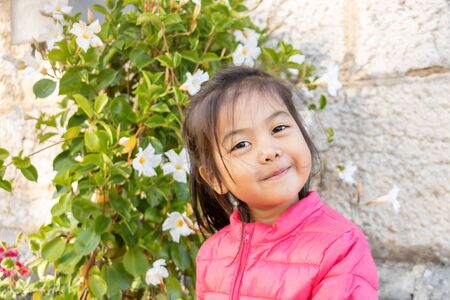 Eurasian half-blooded Eurasian girl smiling in front of a blooming grove? Portrait