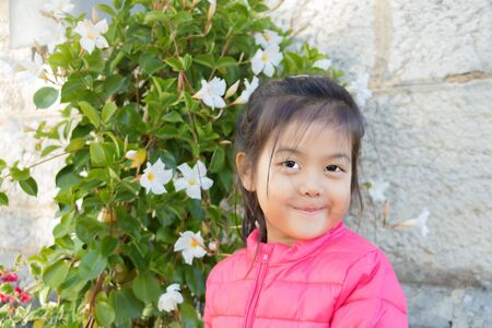 Little Eurasian Chinese girl posing timidly in front of a blooming grove? Portrait