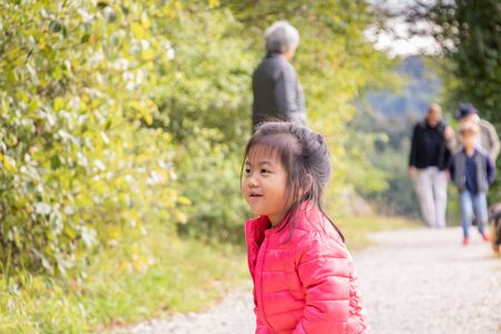 Little Eurasian Chinese and French girl happy with her family in the forest in autumn? Portrait 写真素材