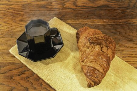Classic breakfast at the cafe with a cup of black coffee and a croissant 写真素材