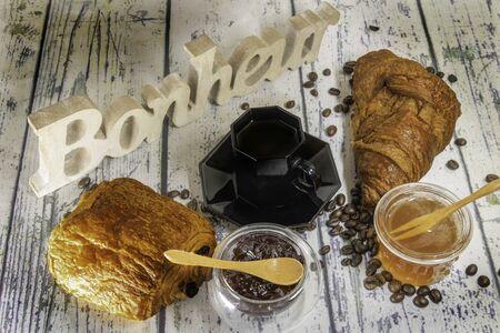 Chocolate bread and pure butter croissant, handcrafted pastries with the word happiness (happiness is happiness written in French) carved in a piece of wood Zdjęcie Seryjne