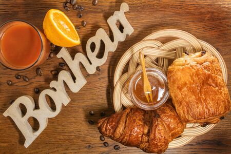 Chocolate bread and butter croissant, pastries in a handmade wicker basketball with the word happiness (Happiness is happiness written in French) carved in a piece of wood on a table with a jar of honey and fruit juice Фото со стока