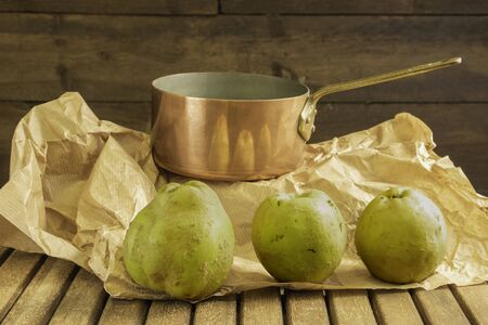 Whole quinces with fluffy skin in front of a copper pan to make old fashioned jam with eco-friendly wrapping paper on a wooden background and table - vintage and rustic 写真素材
