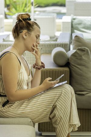Pretty young woman smoking a cigarette on a patio and phoning a customer on her smartphone