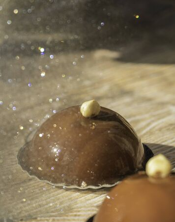 Reflection of a chocolate and praline dome-shaped opera cake with a hazelnut in a glitter mirror with a wood background