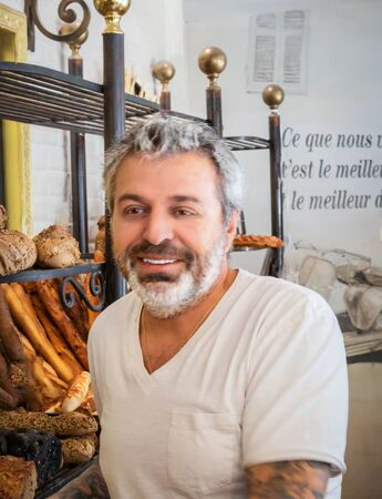 Handsome mature bearded male bartender proudly smiling at camera, working in his bakery shop. Friendly baker hipster and tattooed in front of his different bread varieties