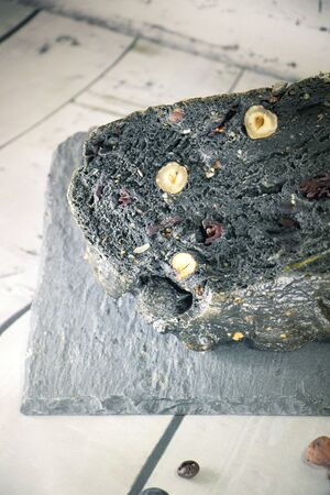 Closeup on a black bread with charcoal cereals and dried fruits set on a white bread slices on a wooden kitchen splashback
