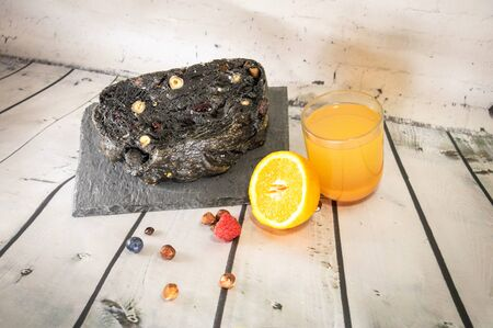 Essential ingredients for the preparation of a healthy breakfast and vitaminized artisan bread with charcoal and dried fruit and cereals squeezed orange juice and seasonal fruits 写真素材