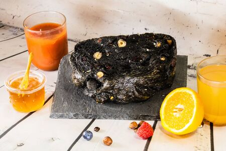 Charcoal black bread and dried fruit on a slate dish by a smoothie and orange juice squeezed with honey and fresh fruit