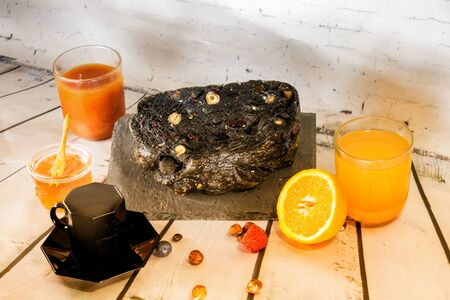 Breakfast preparation with a tomato juice and a fresh orange juice honey fresh seasonal fruit and a black bread with charcoal cereals and dried fruits