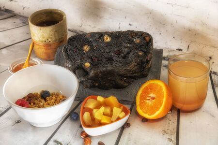Full breakfast with a varied and healthy diet - Bowl of cereals with fresh seasonal fruit raspberries, pineapple mango and blackcurrant orange juice squeezed honey tea charcoal bread 写真素材