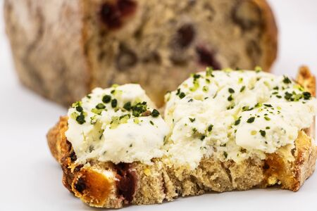 Fresh goat cheese slices with herbs garlic and chopped mustots on a slice of bread with cereals and dried fruits background