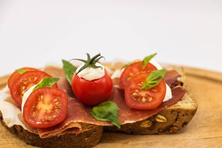 Italian sandwich on a slice of multigrain bread with a slice of red ham on a white background mozzarella on a slice of bread on a wooden background - isolated white background 写真素材