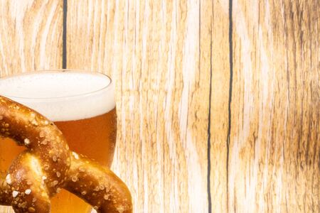 Graphic resource with negative space for text for the Oktober Fest with a light wood background and a glass of beer and a giant pretzel at an angle 写真素材