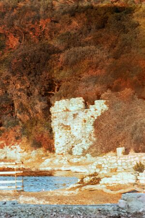 Indian summer in Corsica, Provence, France with a vegetaation reddened by the arrival of autumn - Edge of the beach with a Genoese tower in ruins and the Corsican maquis