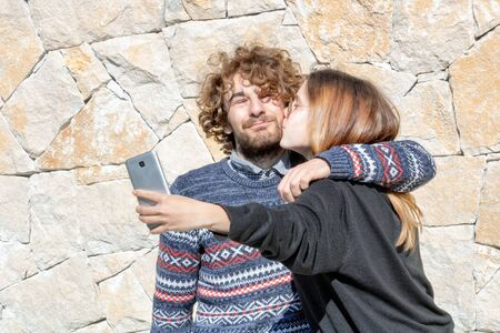 Young couple taking a selfie with their smartphone while making a kiss - Young happy and smiling couple