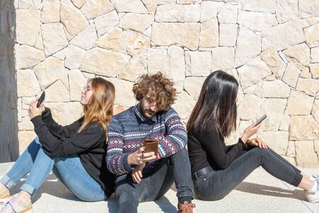 3 young people - one man and two women - turning their backs and their smartphone sitting on the ground